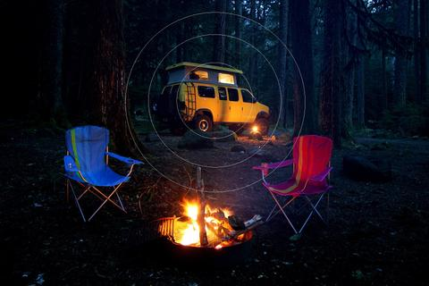 RV Cell Phone Signal Booster - Van with pop-up camper parked in the woods by a campfire