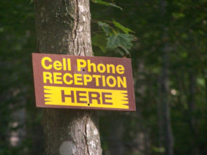 Sign in the woods on a tree reads Cell Phone Reception Here