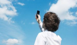 Improve Cell Phone Signal - Young man holding his phone to the sky