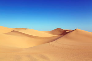 How Temperature Affects Mobile Signal - Smooth brown sand in a desert against a bright blue sky