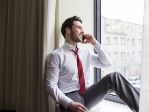 Are Cell Phone Boosters Worth It? - Businessman on phone by a window